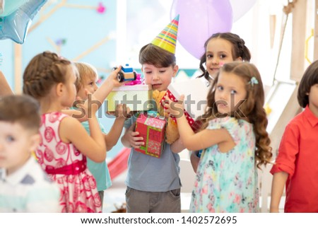 Group of diversity children party together. Kids giving gift boxes to boy during birthday party in daycare or entertainment centre