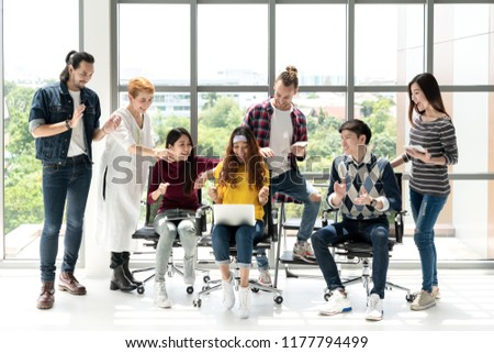 Group of Diversity People Team smiling and excited in success work with laptop at modern office. Creative Multi ethnic or diverse teamwork feeling happy, enjoy and engaged with achievement project.