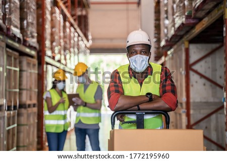 Group of diversity Workers wearing protective face mask working in factory warehouse. Black man pushing metal lathe cart with box parcel during covid 19 pandemic crisis. Logistic industry concept.