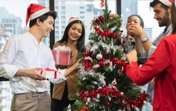 Group of diversity young creative happy celebrating Merry Christmas and Happy New Year decorating Christmas tree in office in modern office