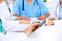 Group of doctors at medical meeting. Close up of physician using tablet computer.