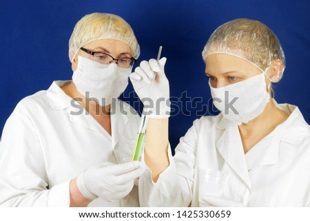 Group of doctors in masks with medical jar on blue background. Chemists doing medical analysis. Medical Research scientist work with test tubes, DNA tests, sperm tests