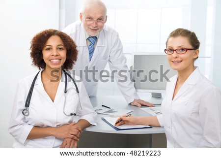 Group of doctors sit on a workplace and look at the camera