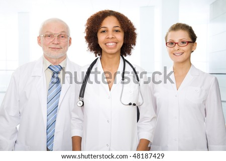 Group of doctors stand in a hall of modern hospital