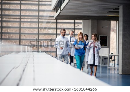 Group of doctors walking in corridor on medical conference.