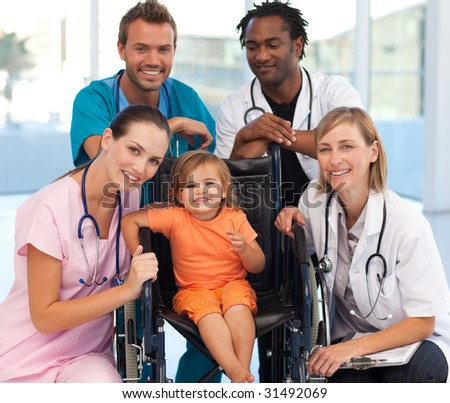 Group of doctors with a baby in a wheelchair smiling at the camera