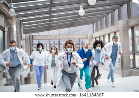 Group of doctors with face masks running, corona virus concept.