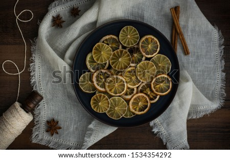 group of dried citrus rounds on plate on white cloth with spices, dehydrated lemon and lime round cut, diy holiday decor, homemade decorations for christmas   #1534354292