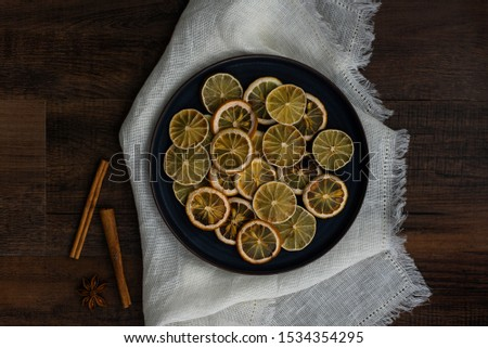group of dried citrus rounds on plate on white cloth with spices, dehydrated lemon and lime round cut, diy holiday decor, homemade decorations for christmas   #1534354295