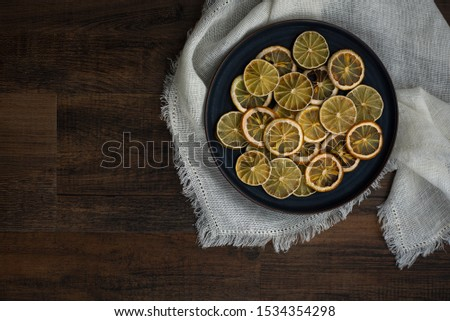 group of dried citrus rounds on plate on white cloth with spices, dehydrated lemon and lime round cut, diy holiday decor, homemade decorations for christmas   #1534354298