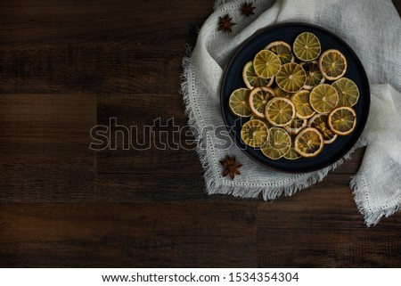 group of dried citrus rounds on plate on white cloth with spices, dehydrated lemon and lime round cut, diy holiday decor, homemade decorations for christmas   #1534354304