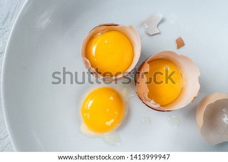 group of egg yolks in broken shells on white background flat lay #1413999947
