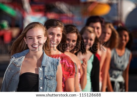 Group of eight girlfriends in a row smiling