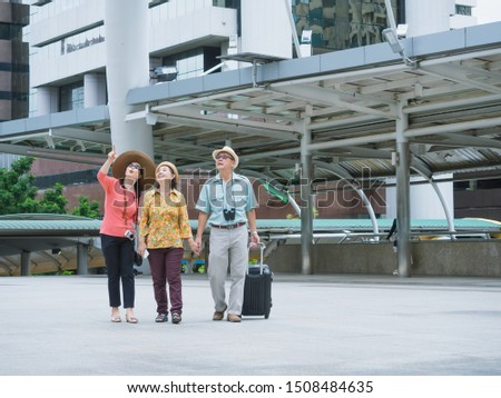group of  elderly are traveling in the city,elder man and elder woman looking and walking around the city
