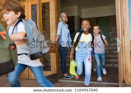 Group of elementary school children running outside at the end of the lessons. Happy school boys and girls running outside from school building. Finish school and summer vacation concept.