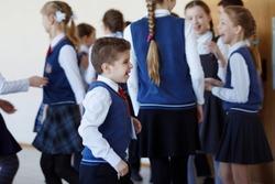 Group of elementary school kids standing in school corridor