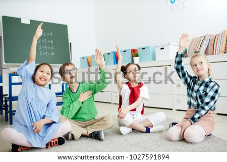 Group of elementary schoolkids raising their hands to answer question of teacher at lesson #1027591894