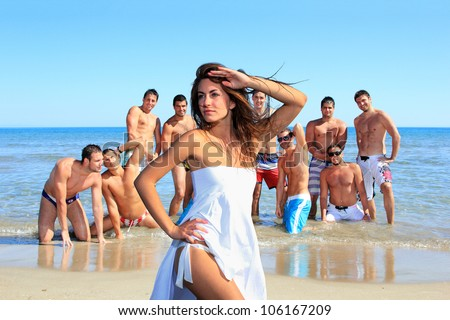 Group of eleven handsome guys on the beach looking at a beautiful girl in bikini