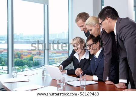 Group of employees in suits at office with the big window