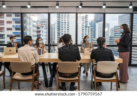 Group of employees sitting at a meeting, wearing a mask, having a leader standing at the head of the table in the meeting, introducing new normal work.