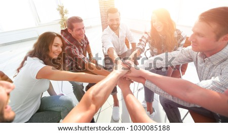 group of employees with hands clasped together. #1030085188