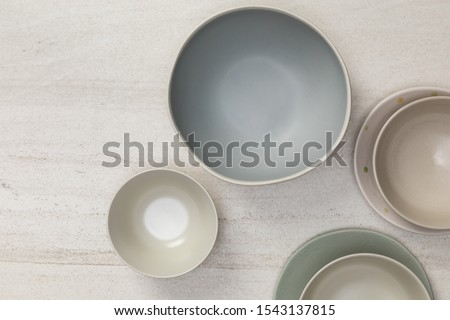 Group of empty blank ceramic round bowls and plates on white stone blackground, Top view of traditional handcrafted kitchenware concept Stock photo ©