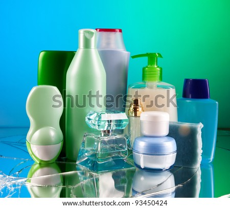 Group of empty cosmetic bottles on beautiful green and blue mirror