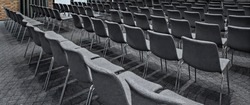 Group of empty gray chairs in modern conference hall - presentation room for seminars