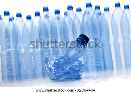 group of empty plastic bottles with crushed one
