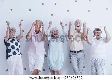 Group of enthusiastic seniors keeping their hands raised against wallpaper with gold dots