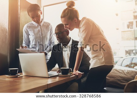 Group of entrepreneurs working using a laptop and holding a document