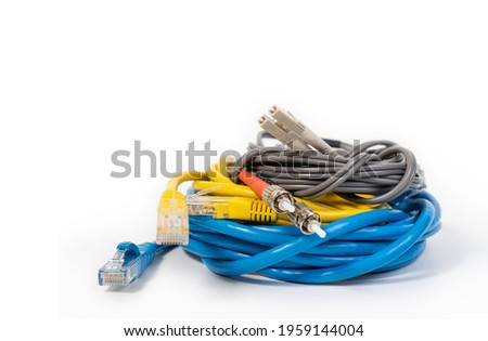 Group of ethernet network cables, rj45 network cable and fiber optic cables isolated on white background. CAT 5, CAT 6, LC and ST type ethernet network cables on white background.