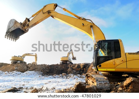 group of excavators loaders at construction site with raised bucket over blue sky in winter