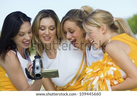 Group of excited cheerleaders watching video on camcorder