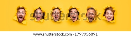 Group of excited hilarious young people with amazed faces looking through ripped holes in bright yellow paper Сток-фото ©