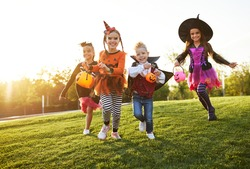 Group of excited kids in spooky costumes smiling and running on lawn during Halloween celebration in evening in park