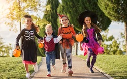 Group of excited kids in spooky costumes smiling and running on path in  during Halloween celebration in evening in park