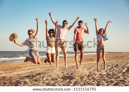 Group of excited young friends dressed in summer clothes holding hands while jumping together at he beach