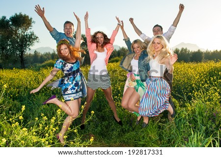 Group of excited young people leaping in the air and celebrating a beautiful hot sunny summer day as they enjoy an outing into the countryside in a colorful yellow rapeseed field