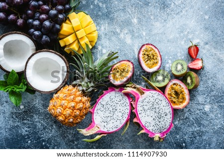 Group of exotic tropical fruits. Mango, dragon fruit, passion fruit, coconut, kiwi, pineapple and strawberry on concrete blue background. Fresh fruit flat lay