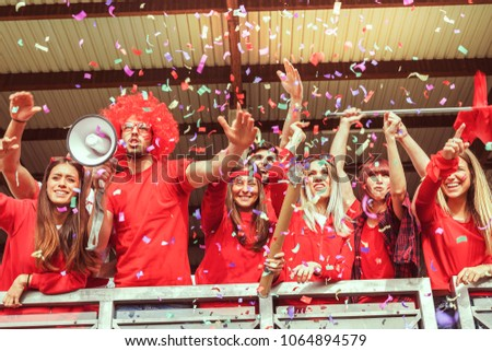 group of fans dressed in red color watching a sports event in the stands of a stadium #1064894579