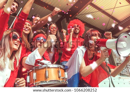 group of fans dressed in red color watching a sports event in the stands of a stadium #1066208252