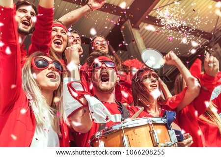 group of fans dressed in red color watching a sports event in the stands of a stadium #1066208255
