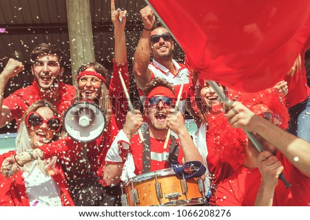 group of fans dressed in red color watching a sports event in the stands of a stadium #1066208276