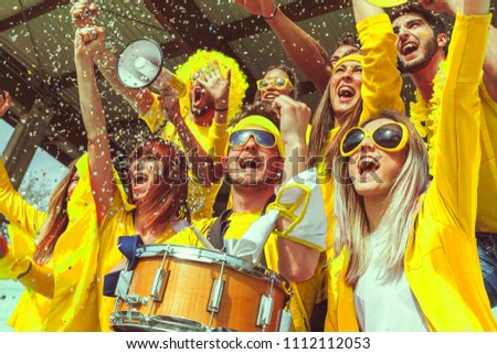 group of fans dressed in yellow color watching a sports event in the stands of a stadium #1112112053