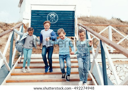 Group of fashion children wearing denim clothing playing on the sea shore. Autumn casual outfit in blue and navy color. 7-8 years old models.