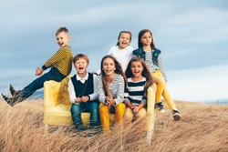 Group of fashion children wearing same style clothing playing on a sofa in the autumn field. Fall casual outfit in navy and yellow colors. 7-8, 8-9, 9-10 years old models sitting on a coach outdoor.