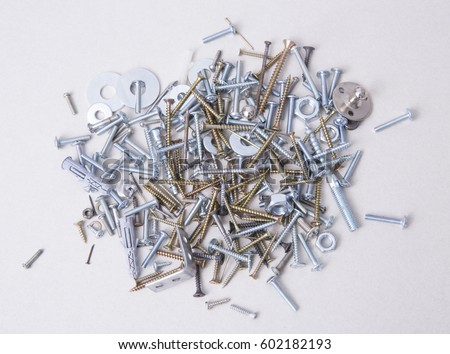 Group of fastening elements bolts, nails, screws, washers, konfirmats, dowels top view on white background.
