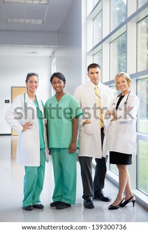 group of female and male doctors and nurses (Caucasian, African American, Hispanic ethnicity) smiling in lab coats and scrubs, in hospital looking at camera
