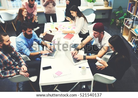Group of female and male IT professionals working on software development using modern devices while sitting at table. Skilled bloggers are copywriting for media web page typing on computer keyboard